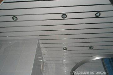 Белый реечный потолок с хромированными вставками в душевой