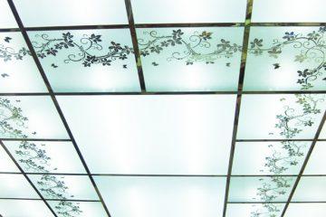 Матовый потолок с зеркальным цветочным декором и серебряными вставками.
