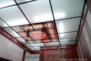 """Матово-зеркальный потолок с декорированными узорами и декором """"Лицо"""" с красной подсветкой."""