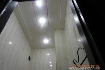 Реечный потолок белого цвета с серебристыми вставками и светильниками